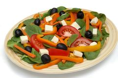 Fresh spinach salad on a plate. A salad of raw spinach with carrots, bell peppers, black olives, tomatoes, and cheese chunks stock photo