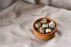 Quail eggs in a wooden bowl on a homespun tablecloth, top view, close-up. Fresh spotted quail eggs in a wooden bowl on a homespun tablecloth, top view, close-up stock images