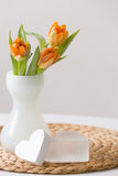 Fresh spring bunch of orange tulips in a nice white glass vase and two cute heart symbols on the straw board. Home decor Royalty Free Stock Images