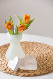 Fresh spring bunch of orange tulips in a nice white glass vase and two cute heart symbols on the straw board. Home decor for sprin Stock Photos