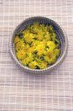 Fresh spring dandelion flower in basket on table Royalty Free Stock Image