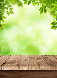 Fresh spring green bokeh background with wooden ta. Empty wooden table in the foreground above, fresh green field in the background Royalty Free Stock Image