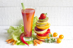 Fresh spring juice and pile of slice fruits and vegetables Royalty Free Stock Photography