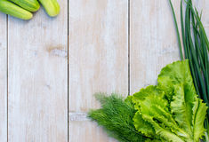 Fresh spring lettuce, green onions and dill , cucumbers and radishes on a light wooden background fresh juicy green , spring green. Cucumbers, juicy lettuce Royalty Free Stock Images