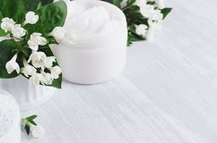 Fresh spring organic spa cosmetics products with small white flowers and green leaves on white wood background, copy space. Fresh spring organic spa cosmetics stock photos