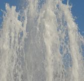 Fresh spring pouring water. Fountain on blue sky. The jet pouring up strong spring water of the fountain is splashing on the blue sky background Royalty Free Stock Photography