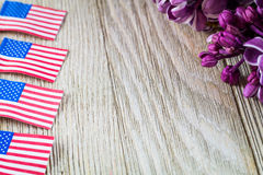 Fresh spring purple lilac and miniature flags on wooden board with room for copy Royalty Free Stock Photo