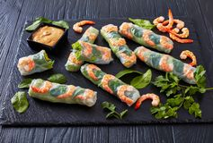 Fresh Spring Roll, Vietnamese Rice Paper Rolls. With lettuce, bean sprouts, vermicelli noodles, mint and shrimps served with peanut dipping sauce on a black stock photography