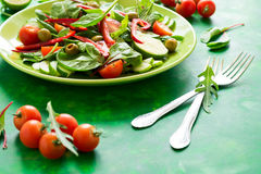 Fresh spring salad with arugula, spinach, beet leaves, tomatoes, cucumber slices and sweet pepper Stock Photos