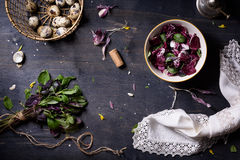 Fresh spring salad with basil, eggs, radicchio leaves and garlic on dark wooden table, top view. Fresh spring purple salad with basil, eggs, radicchio leaves Royalty Free Stock Image