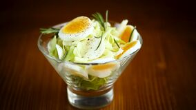 Fresh spring salad with cabbage, lettuce and boiled eggs with rosemary and spices