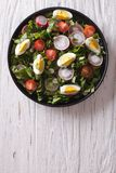Fresh spring salad with eggs vertical top view. Fresh spring salad with eggs, tomato, radish and herbs on a plate. vertical top view royalty free stock photo