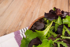Fresh spring salad. Fresh green salad with spinach, arugula, romaine and lettuce in a bowl on rustic wooden background royalty free stock image