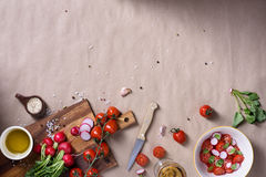 Fresh spring salad with tomatoes, radishes and spicy seasoning. Raw ingredients over rustic background, space for text. Top view Stock Photos