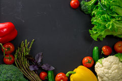 Fresh spring vegetables on black chalkboard. Background layout with free text space Stock Image