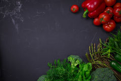 Fresh spring vegetables on black chalkboard. Background layout with free text space Royalty Free Stock Photos
