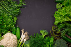 Fresh spring vegetables on black chalkboard. Background layout with free text space Royalty Free Stock Images