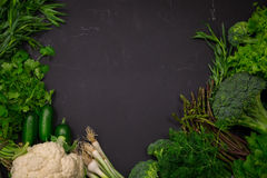 Fresh spring vegetables on black chalkboard. Background layout with free text space Royalty Free Stock Image