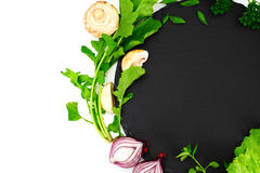 Fresh Spring Vegetables, Greens and Empty Black Plate with Place Stock Photography