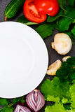Fresh Spring Vegetables, Greens and Empty White Plate with Place Stock Photo