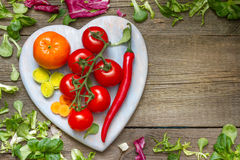 Fresh spring vegetables on wooden heart Royalty Free Stock Image