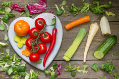 Fresh spring vegetables on wooden heart Stock Photography