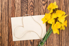 Fresh  spring yellow  daffodils  flowers and empty tag on brown painted wooden planks. Selective focus. Place for text. Fresh  spring yellow  daffodils  flowers Stock Photography