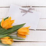 Fresh  spring yellow tulips flowers and tag on white  painted wo Royalty Free Stock Photo