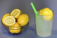 Free Fresh Squeezed Lemonade With A Green Straw Next To A Bowl Of Lemons. Stock Photo - 179991710