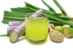 Fresh squeezed sugar cane juice. Fresh squeezed sugar cane juice in clear glass with cut pieces cane and brown sugar on white background Stock Photos