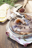 Fresh squid carcass in a glass pot with herbs. And sliced lemon royalty free stock image