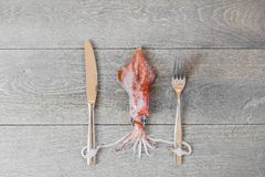 Fresh squid on wooden table with fork and knife Royalty Free Stock Photography