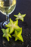 Fresh starfruit and a drink in a glass on black background Stock Images