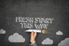 Fresh start this way concept. On black blackboard with businessman hand holding paper plane Royalty Free Stock Photography
