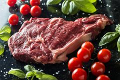 Fresh steak served with spices, tomatoes and leafs of basil on marble background. Uncooked beefsteak cooking on a Royalty Free Stock Photo