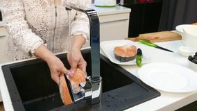 Fresh steak of trout under water in the hands of an old woman. stock footage