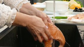 Fresh steak of trout under water in the hands of an old woman. stock video footage