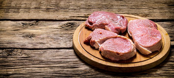 Fresh steaks on an old wooden Board. On wooden background. Free space for text Stock Photography