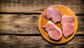 Fresh steaks on an old wooden Board. On wooden background. Free space for text . Top view Stock Image