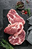 Steaks from Raw pork meat. Fresh steaks from Raw pork meat on dark stone background, Top view Stock Images