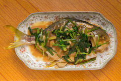 Fresh steamed whole fish covered with herbs onions & sauce Stock Photography