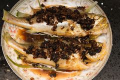 Fresh steamed whole fish covered with herbs onions & sauce Stock Image