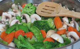 Fresh Stir fry vegetables in pan with wooden spoon. Brocolli, mushrooms, carrots, peas onions in a silver pan with slotted wooden spoon for a healthy dinner royalty free stock photography