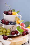 Fresh stone fruits and cherries in cups. Fresh stone fruits cherries peaches plums in stacked white cups Stock Images