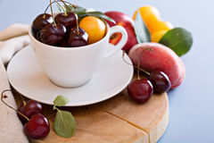 Fresh stone fruits and cherries in white cup Royalty Free Stock Images