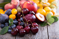 Fresh stone fruits on wooden table. Fresh stone fruits cherries peaches plums on wooden table royalty free stock photography