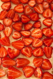 Fresh strawberries. Strawberries cut in half and places on a vanilla bedding Royalty Free Stock Images
