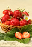 Fresh strawberries. Strawberries on a wooden basket and green leaves Royalty Free Stock Image