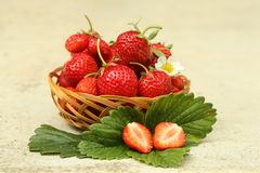 Fresh strawberries. Strawberries on a wooden basket and green leaves Stock Photo