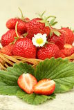 Fresh strawberries. Strawberries on a wooden basket and green leaves Stock Image